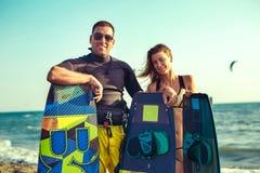 享受在海滩的俏丽的微笑的夫妇kitesurfer夏令时 免版税库存图片
