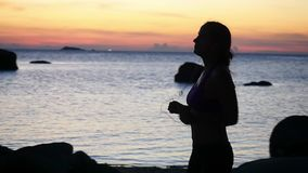 享受在海滩的年轻女人剪影日落奔跑与耳机 慢的行动 1920x1080 股票录像