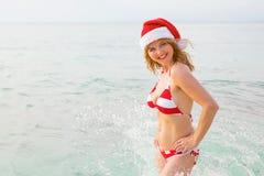 享受在海滩的愉快的妇女圣诞节假期 免版税库存图片