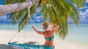 享受在海滩的愉快的美丽的无忧无虑的妇女阳光 性感的红色桃红色比基尼泳装的少妇在马尔代夫的白色沙滩 免版税图库摄影