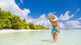 享受在海滩的愉快的美丽的无忧无虑的妇女阳光 性感的红色桃红色比基尼泳装的少妇在马尔代夫的白色沙滩 免版税库存照片