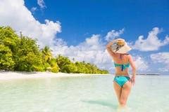 享受在海滩的愉快的美丽的无忧无虑的妇女阳光 性感的红色桃红色比基尼泳装的少妇在马尔代夫的白色沙滩 免版税库存图片