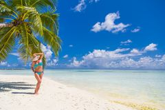 享受在海滩的愉快的美丽的无忧无虑的妇女阳光 性感的红色桃红色比基尼泳装的少妇在马尔代夫的白色沙滩 库存照片