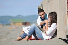 享受在海滩的新夫妇野餐 库存照片