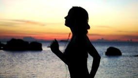享受在海滩的运动年轻女人剪影日落奔跑与耳机 慢的行动 1920x1080 股票录像