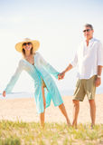享受在海滩的中世纪夫妇步行 免版税库存图片