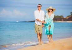 享受在海滩的中世纪夫妇步行 图库摄影