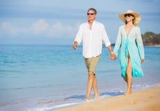 享受在海滩的中世纪夫妇步行 库存图片