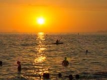 享受在海滩的人们日落在里约热内卢 免版税库存图片