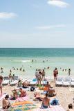 享受在海滩的人们热天气 免版税库存图片