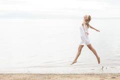 享受在海滩的可爱的妇女的幸福夏天 库存图片
