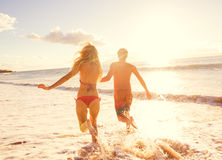 享受在海滩的夫妇日落 免版税库存图片