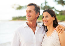 享受在海滩的成熟夫妇日落 免版税库存图片