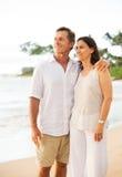 享受在海滩的成熟夫妇日落 库存照片