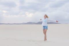 享受在海滩的无忧无虑的妇女自由 免版税库存图片