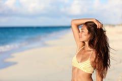 享受在海滩的无忧无虑的比基尼泳装妇女日落 免版税库存照片
