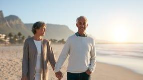 享受在海滩的资深夫妇漫步 免版税图库摄影
