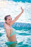 享受在游泳池的愉快的少妇夏令时 免版税库存图片