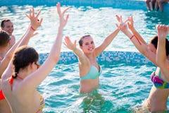 享受在游泳池的愉快的朋友夏令时 图库摄影