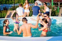 享受在游泳池的愉快的朋友夏令时 免版税库存照片