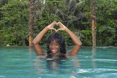 享受在热带手段无限水池的年轻可爱的愉快的黑人非裔美国人的妇女假日对美丽的密林landsca 免版税库存照片