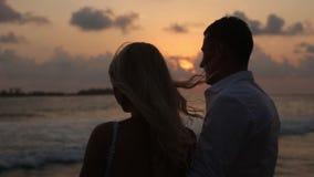 享受在热带海滩的后面观点的新娘和新郎日落在楼梯栏杆附近在度假 拥抱的新婚佳偶和 股票录像