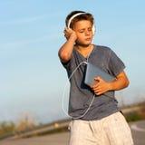 享受在片剂的男孩音乐户外。 库存图片