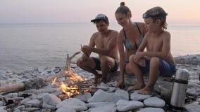 享受在狂放的海滩的幸福家庭夏天日落在篝火附近 股票录像