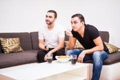 享受在电视的朋友足球与饮料和快餐在沙发 免版税库存图片