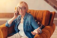 享受在电话的正面资深妇女一次谈话 免版税图库摄影
