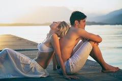 享受在码头的夫妇日落光 免版税图库摄影