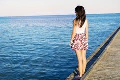 享受在码头的自由的妇女海视图 免版税图库摄影