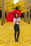 享受在秋叶的深色的模型一秋天天与一把红色伞 库存图片