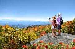 享受在秋天山的人们美丽的景色 免版税库存照片