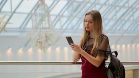 享受在立体声辅助部件的快乐的青少年的女孩画象音乐被连接到招待在咖啡休息的智能手机 股票录像