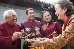 享受在繁体中文衣物的家庭中国膳食 库存照片