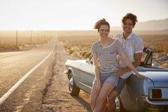 享受在经典汽车的浪漫夫妇画象旅行 库存照片