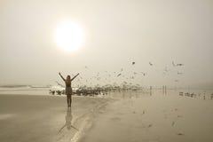 享受在美丽,有雾的海滩的女孩时间 免版税库存照片