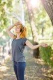 享受在耳机的可爱的女孩音乐摆在公园背景 概念现有量矿穴放松手表腕子 复制空间 免版税库存照片
