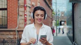 享受在耳机的夫人画象音乐使用走的智能手机户外 股票录像