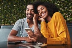 享受在耳机的年轻夫妇听的音乐 库存照片