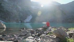 享受在蓝色山湖的男性旅客美丽的景色 股票录像