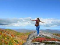 享受在远足的女孩旅行的时间在山顶部 库存图片