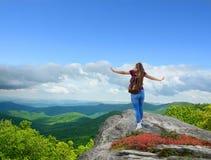 享受在远足的女孩旅行的时间在山顶部 免版税库存图片