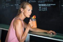 享受在酒吧的俏丽,少妇一份刷新的饮料 免版税库存照片
