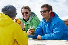 享受在酒吧的小组年轻人饮料在滑雪胜地 图库摄影