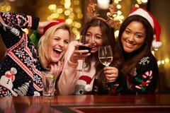 享受在酒吧的小组女性朋友圣诞节饮料 图库摄影