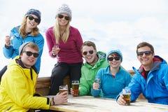 享受在酒吧的小组朋友饮料在滑雪胜地 库存照片