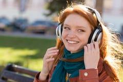 享受在长凳的愉快的微笑的夫人音乐在公园 免版税库存照片