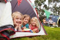 享受在露营地的三个女孩野营假日 免版税库存照片